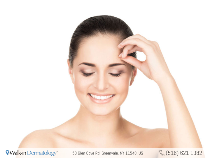 smiling woman touching her forehead